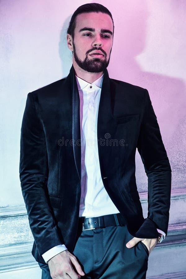 O modelo do homem de negócios vestiu-se no terno preto elegante que levanta no fundo do estúdio fotos de stock royalty free