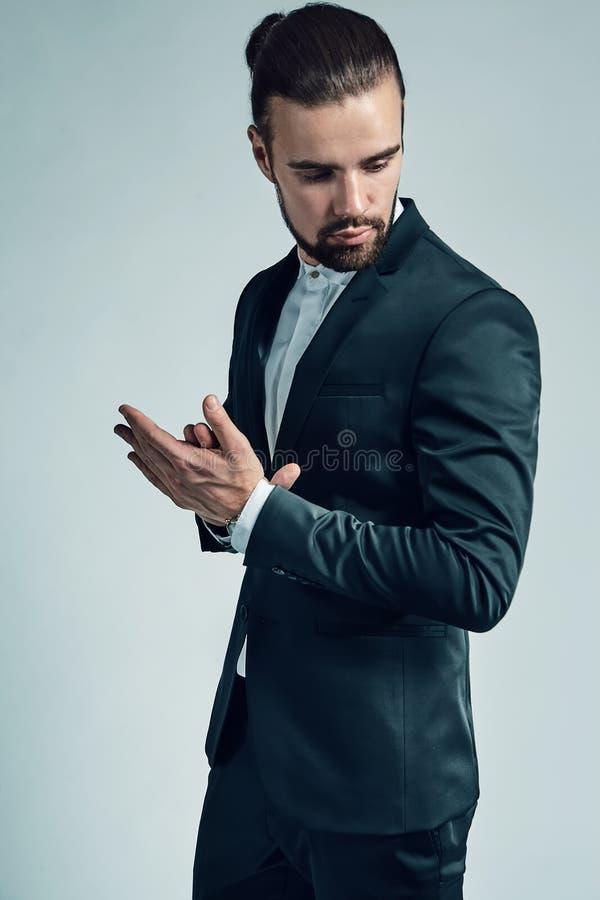 O modelo do homem de negócios vestiu-se no terno preto elegante que levanta no fundo do estúdio imagem de stock