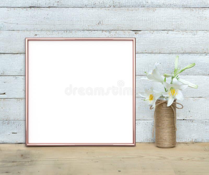 O modelo do quadro do quadrado de Rose Gold perto de um ramalhete dos lírios está em uma tabela de madeira em um fundo de madeira foto de stock