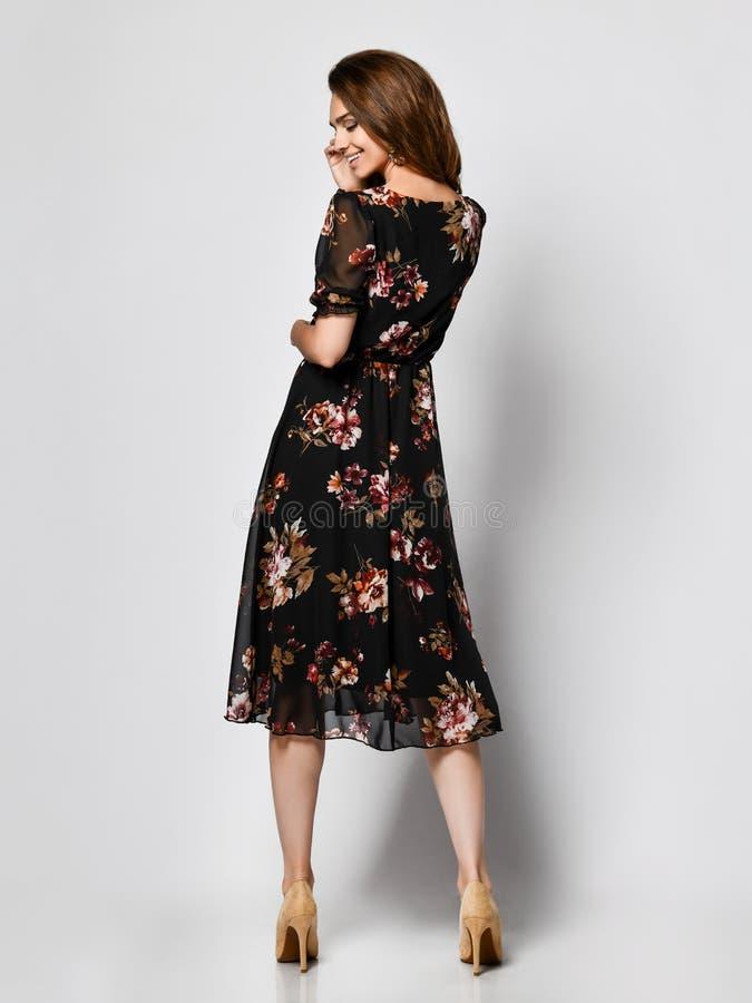 O modelo fêmea encaracolado magro está para trás em um vestido escuro pálido de seda no crescimento completo A menina bonita na r imagens de stock