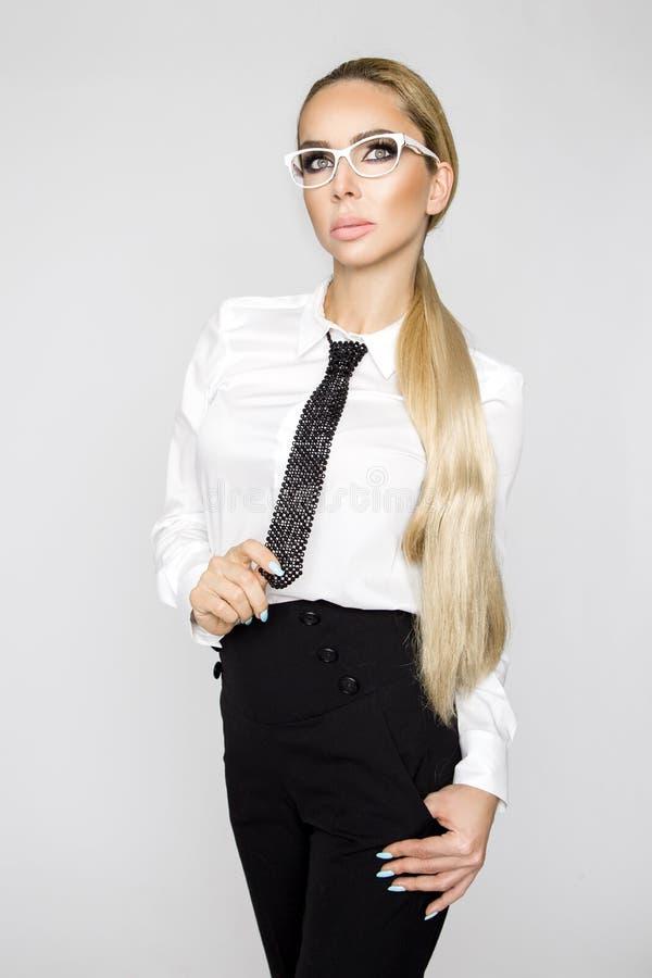 O modelo fêmea louro bonito, elegante, 'sexy' vestiu-se nas camisas e o laço branco e calças pretas foto de stock