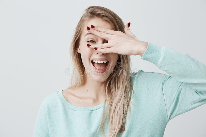 O modelo fêmea louro de sorriso contente que esconde sua cara atrás da mão, tem o sorriso largo, feliz receber cumprimentos de imagens de stock