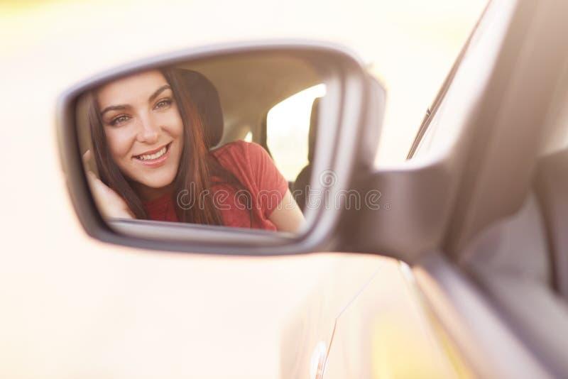 O modelo fêmea novo atrativo com sorriso delicado, olhares no espelho da vista lateral no carro, vestiu-se na roupa vermelha, con fotos de stock