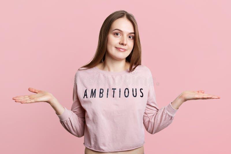 O modelo fêmea novo bonito com expressão hesitante e confundida, encolhos de ombros empurra, pode o ` t fazer a escolha difícil,  foto de stock