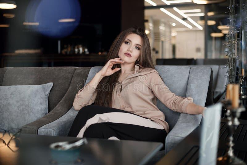 O modelo feliz de sorriso da beleza com natural comp?e e sorrisos longos das pestanas no caf? imagem de stock