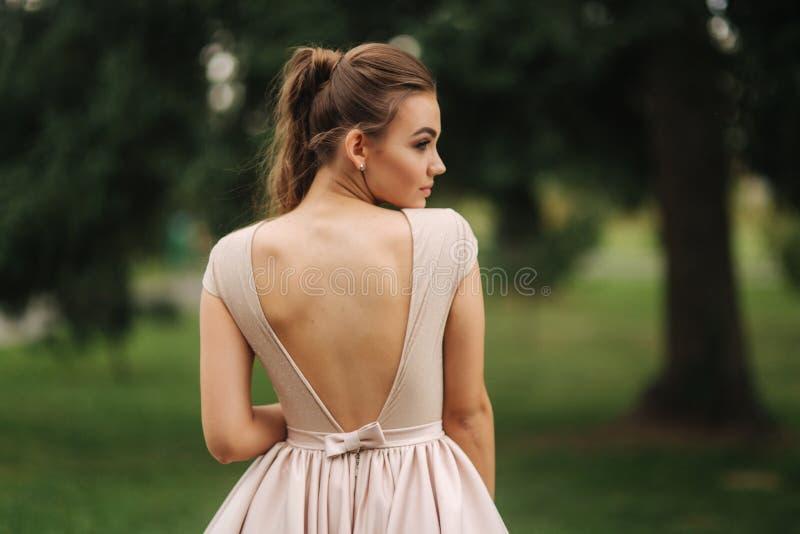 O modelo fino do glamoorus senta-se no banco no vestido de noite fotografia de stock royalty free