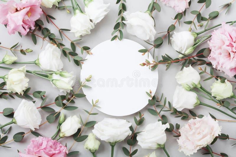 O modelo floral bonito de flores pasteis e do eucalipto verde sae na opinião de tampo da mesa cinzenta Cartão liso da configuraçã imagem de stock royalty free