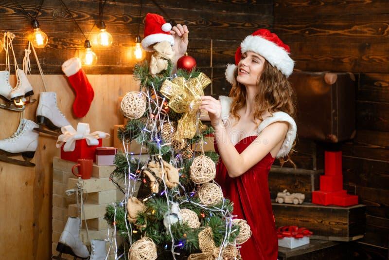 O modelo Girl da beleza em Santa Hat no projeto da casa decora Amigável e alegria Povos felizes Decorações e presente do Natal imagens de stock royalty free