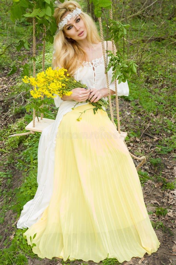 O MODELO LOURO da mulher sensual nova bonita SENTA-SE em vestido surpreendente em um balanço suspendido da ÁRVORE fotografia de stock royalty free