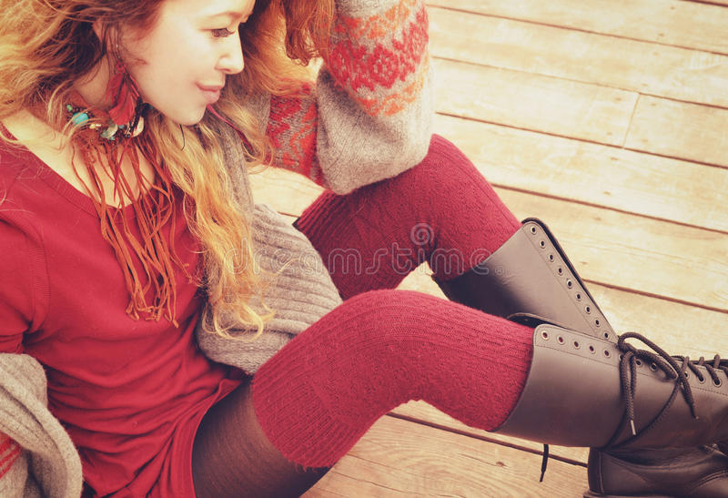 O modelo magro novo da mulher vestiu-se em meias feitas malha mornas e em botas até o joelho, colar feito à mão, foto de stock