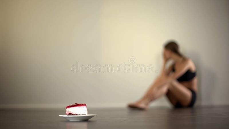 O modelo magro sente a náusea ao olhar o bolo, anorexia, distúrbio alimentar fotografia de stock royalty free