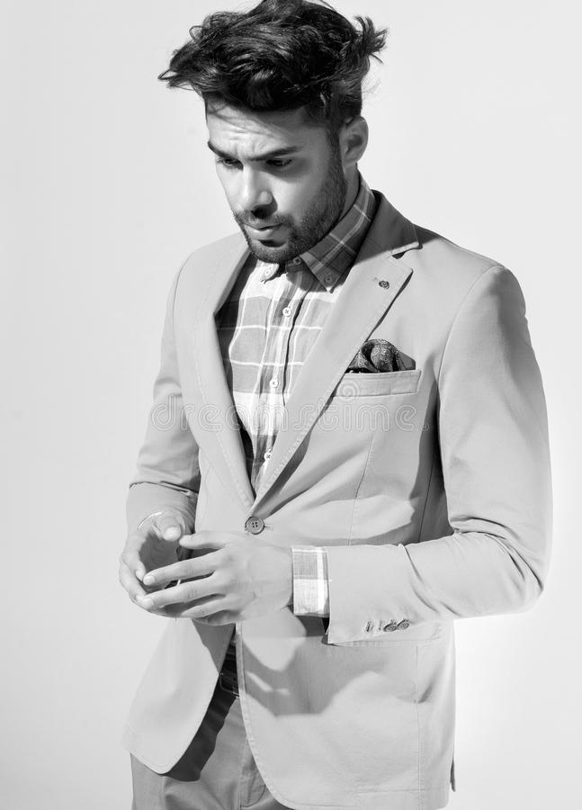 O modelo masculino da forma atrativa vestiu elegante - levantamento ocasional contra a parede fotografia de stock