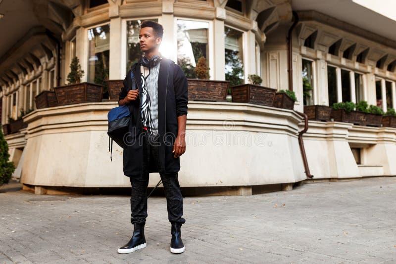 O modelo masculino do moderno na roupa ocasional levanta seguro na rua perto das constru??es Estudante que viaja no conceito novo fotografia de stock royalty free