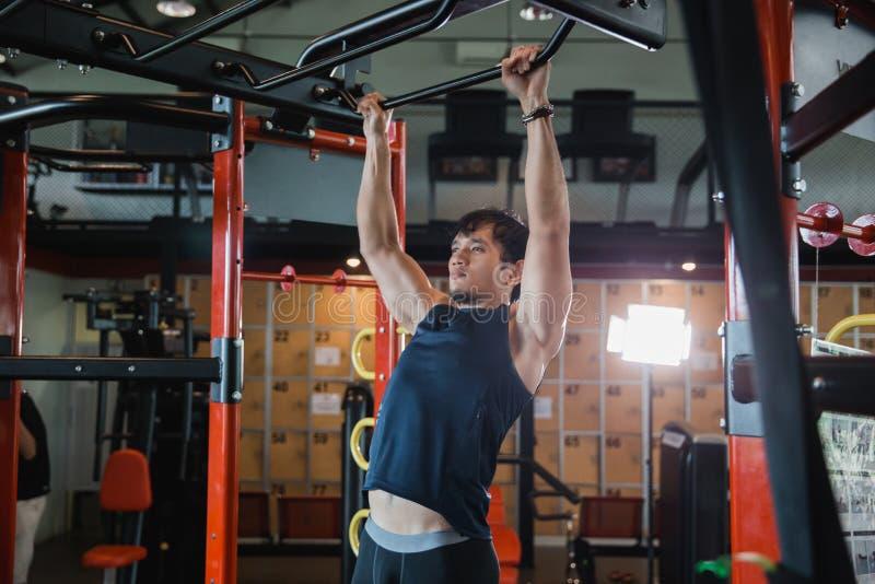 O modelo masculino muscular com o corpo perfeito que faz a tração levanta imagens de stock royalty free