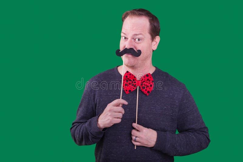 O modelo masculino que guarda o bigode falsificado para enfrentar o suporte vermelho da cabine da foto do bowtie capturou um fund fotos de stock