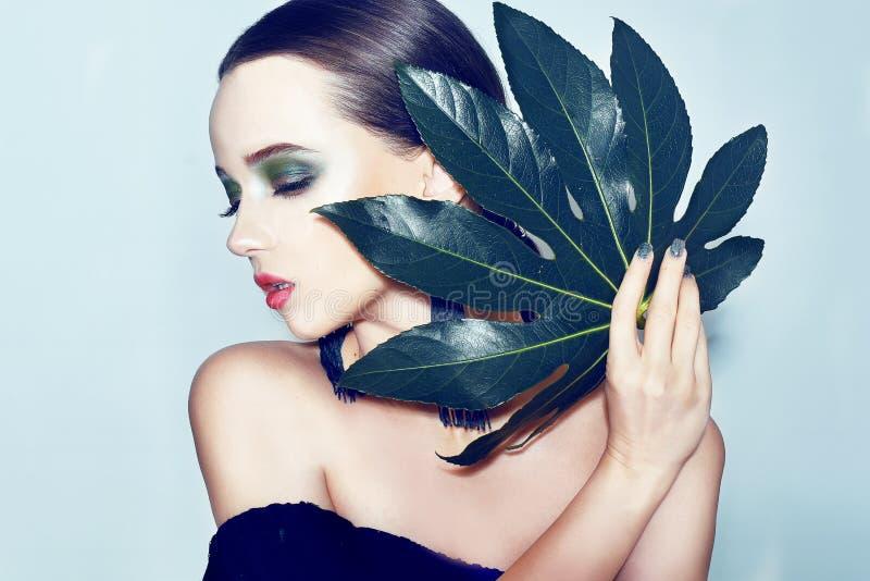 O modelo moreno da beleza 'sexy' com verde e o azul compõem e as folhas verdes Copie o espaço Feche acima, foco seletivo Menina t fotos de stock