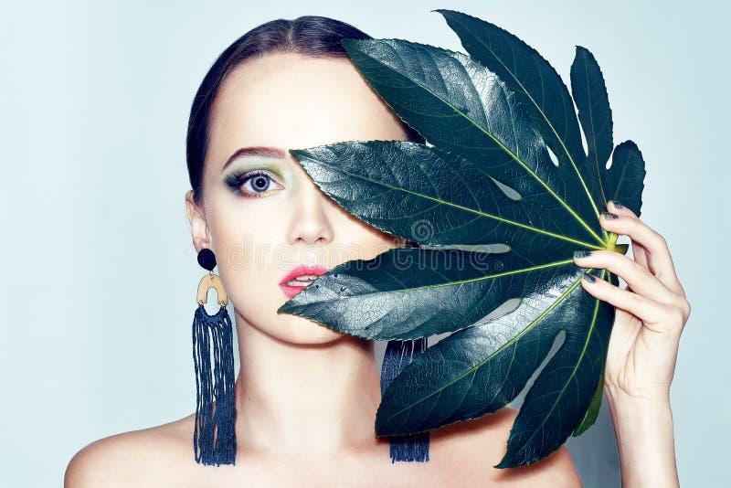 O modelo moreno da beleza 'sexy' com verde e o azul compõem e as folhas verdes Copie o espaço Feche acima, foco seletivo Menina t imagens de stock