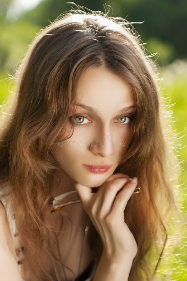 O modelo novo bonito da menina do estudante que veste um vestido senta-se em um mea fotos de stock royalty free
