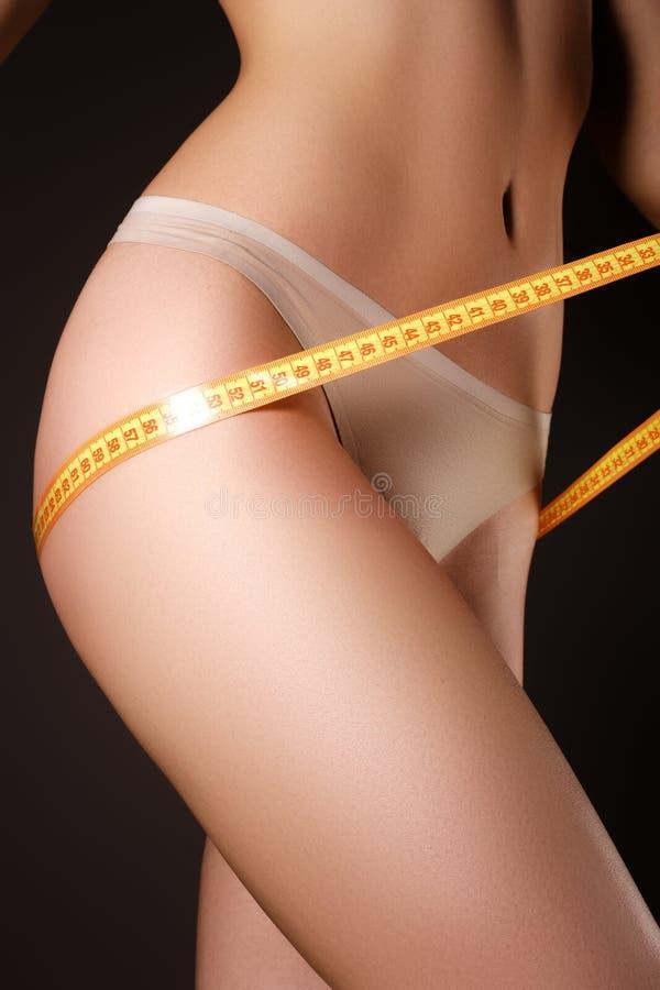 O modelo novo com esportes figura a medição de seus quadris Modelo magro mim fotos de stock royalty free