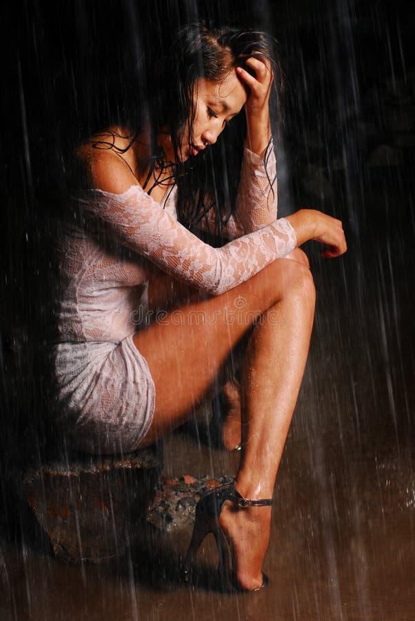 O modelo novo no vestido e nas sapatas da guipura senta-se em uma rocha Pés na água sob a chuva fotografia de stock