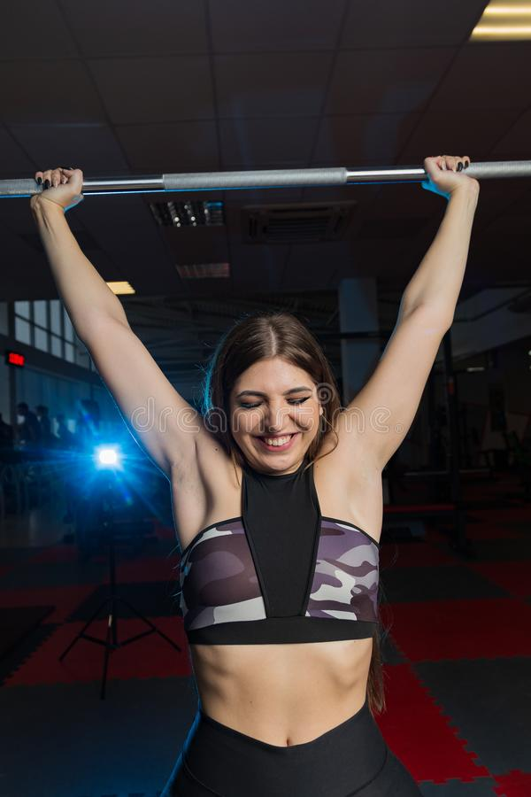 O modelo 'sexy' bonito da aptidão agita um barbell que senta-se atrás da cabeça no gym imagens de stock