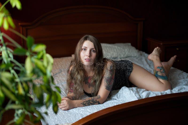 O modelo 'sexy' do tamanho positivo com tatuagens encontra-se em uma grande cama imagens de stock royalty free