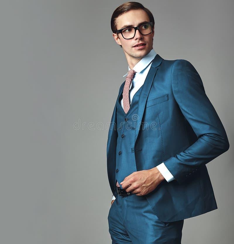 O modelo vestiu-se no terno azul elegante que levanta no fundo cinzento no estúdio nos vidros fotos de stock royalty free