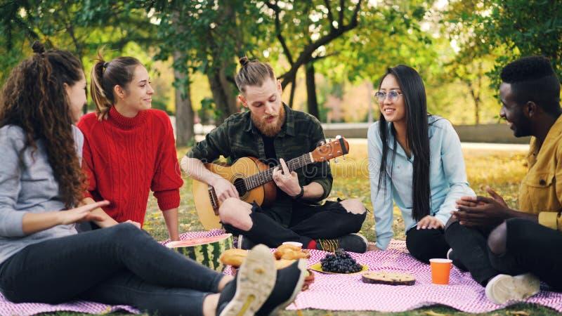 O moderno alegre é de canto e jogando a guitarra que senta-se na cobertura no parque com amigos e que tem o divertimento, os povo fotos de stock royalty free