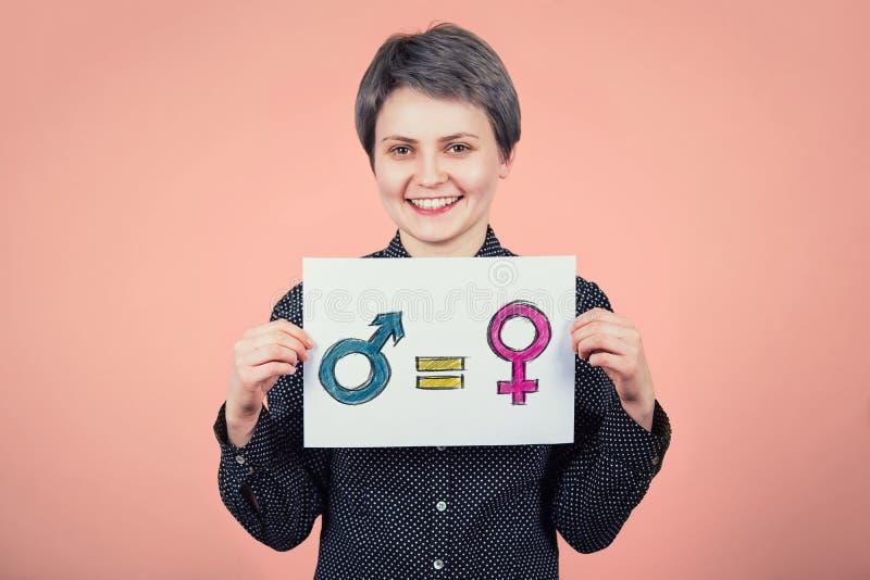 O moderno bonito da jovem mulher que guardam uma folha do Livro Branco com mensagem para o conceito da igualdade de gênero como o foto de stock