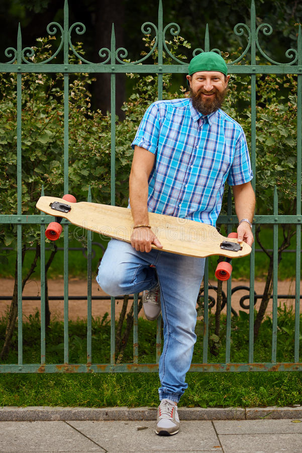 O moderno de sorriso equipa o levantamento com longboard e no tampão verde elegante imagens de stock