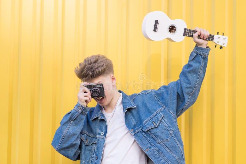 O moderno em um revestimento da sarja de Nimes guarda a uquelele em suas mãos e toma imagens em uma câmera velha do filme fotos de stock