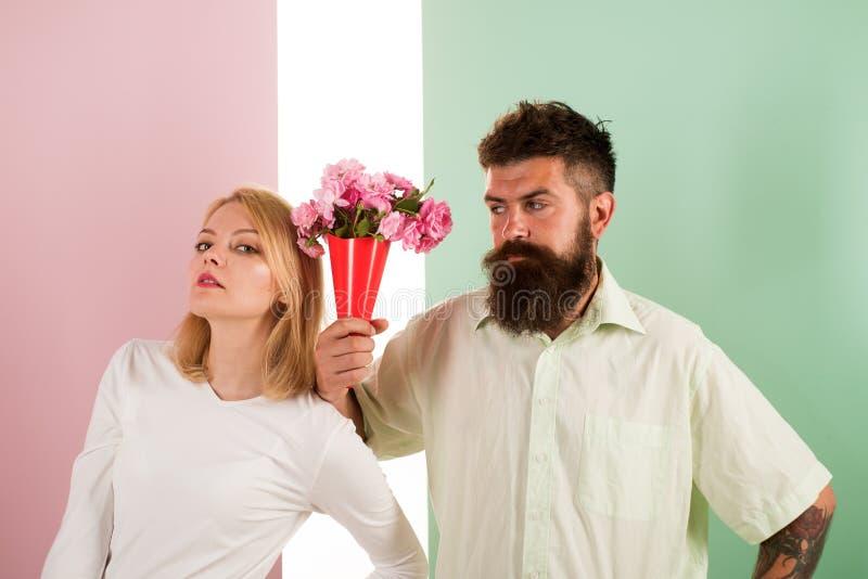 O moderno farpado dá o gesto da desculpa da menina de flores do ramalhete Homem com a mulher dos apologyes da barba Flores do ram foto de stock royalty free