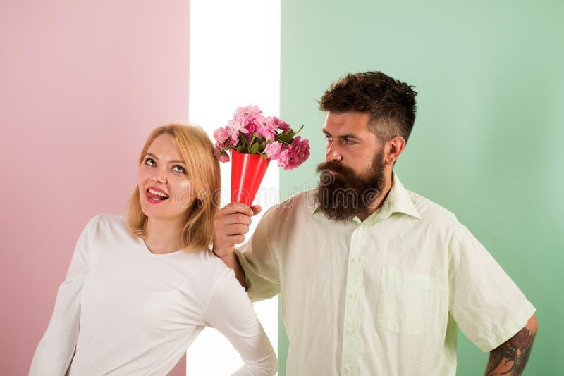 O moderno farpado dá o gesto da desculpa da menina de flores do ramalhete Homem com a mulher dos apologyes da barba Pares no prob fotos de stock royalty free