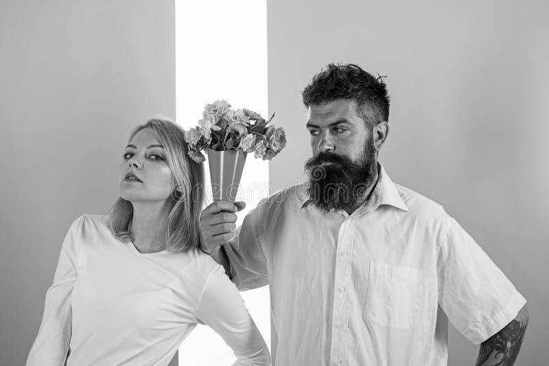 O moderno farpado dá o gesto da desculpa da menina de flores do ramalhete Homem com a mulher dos apologyes da barba Flores do ram imagem de stock royalty free