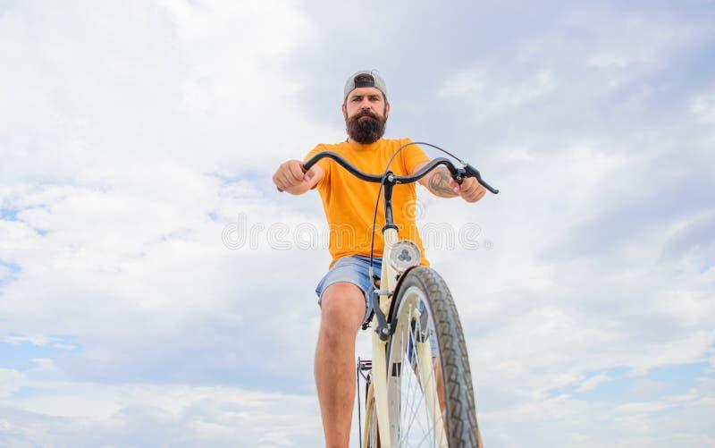 O moderno farpado do homem monta o fundo do céu da opinião inferior da bicicleta Conselho dos mecânicos da bicicleta A bicicleta  fotos de stock royalty free
