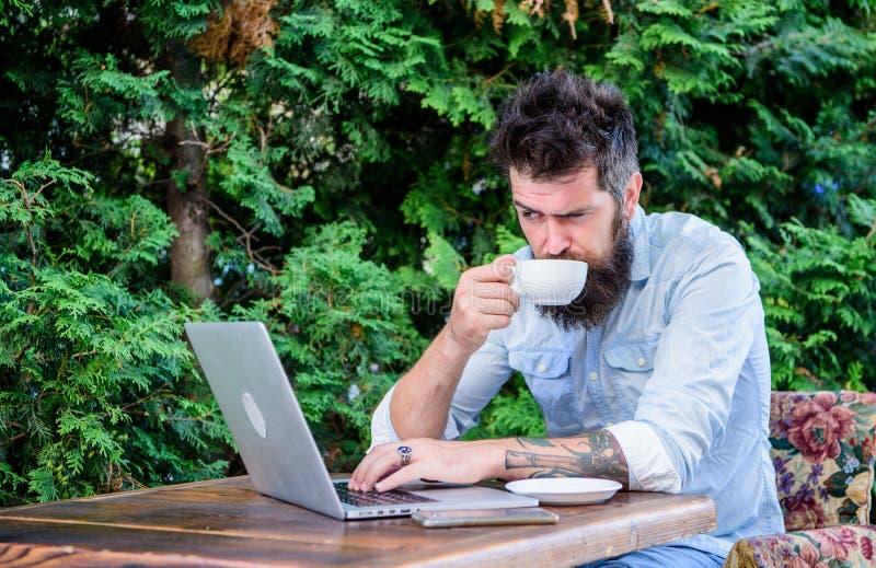 O moderno farpado do homem senta-se fora com Internet surfando do portátil e café bebendo Apartamento do livro em linha Vista do  fotos de stock royalty free