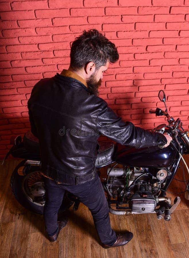 O moderno, motociclista brutal no casaco de cabedal senta-se para baixo na motocicleta, vista traseira Homem com barba, motocicli imagens de stock