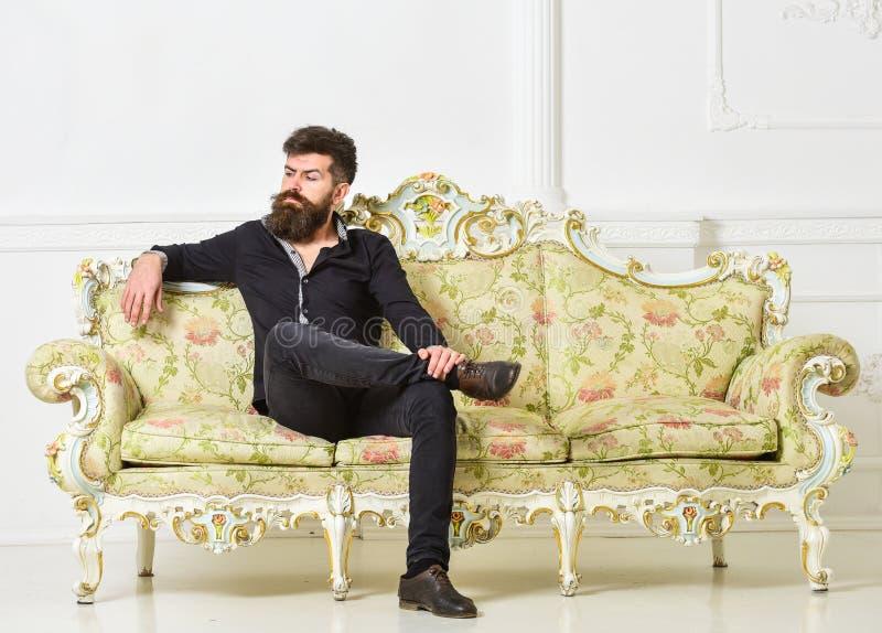 O moderno na cara arrogante senta-se apenas O homem com barba e bigode gasta o lazer na sala de visitas luxuosa Rico e só fotos de stock royalty free