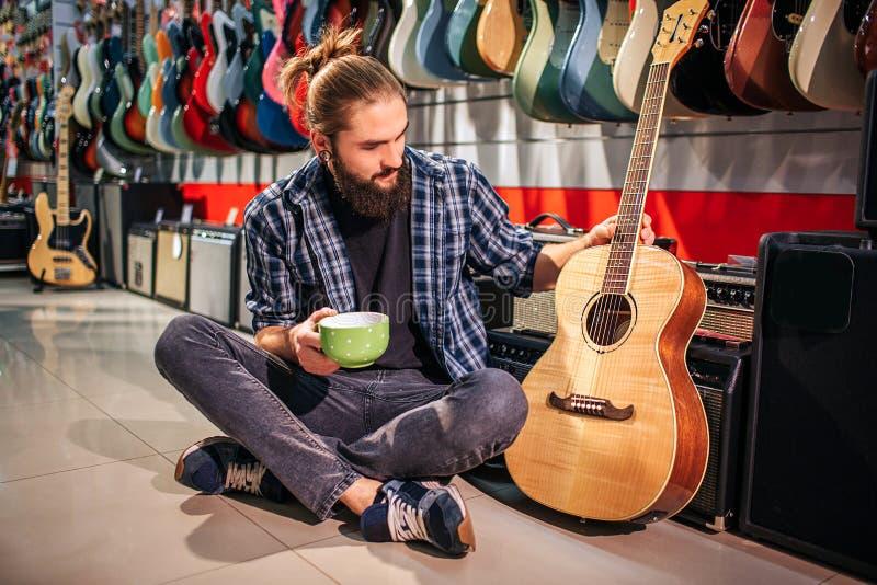 O moderno novo tem o resto sentando no assoalho Guarda o copo à disposição Outro toca na guitarra acústica próxima ele novo imagens de stock royalty free
