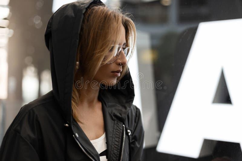 O moderno ruivo 'sexy' da jovem mulher em vidros à moda em um revestimento encapuçado elegante está estando em um shopping fotografia de stock royalty free