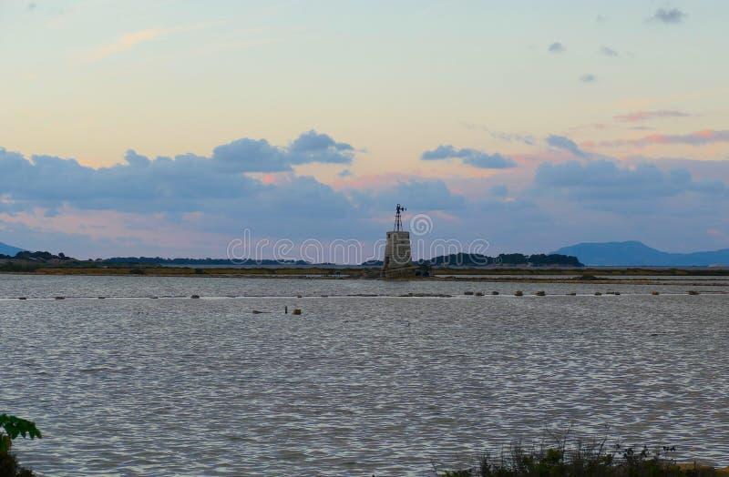 O moinho de vento e as ilhas de Egadi no fundo em Sicília, Itália fotografia de stock