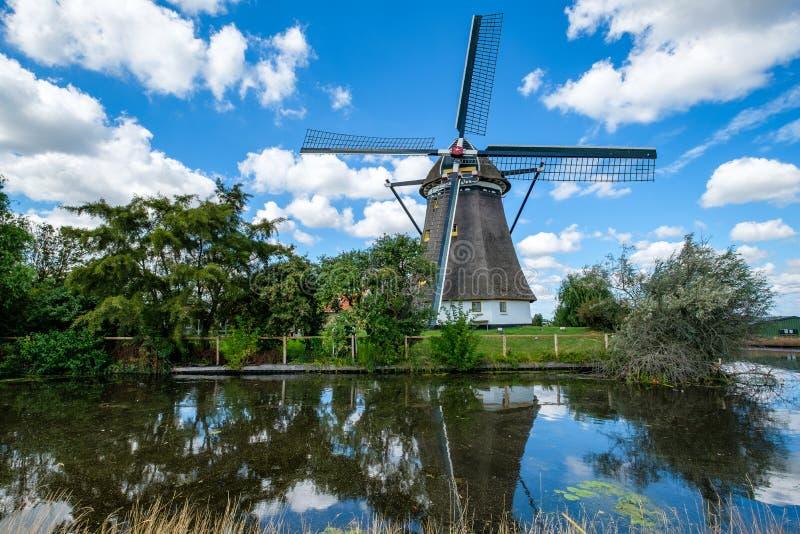 O moinho de vento holandês refletiu na água e no céu azul nebuloso fotografia de stock