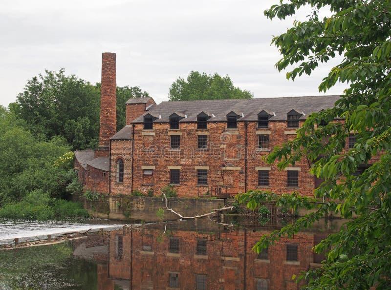 O moinho leeds de Thwaite construiu em 1825 em uma ilha entre o Rio Aire e o canal da navegação de calder refletiu na água fotos de stock royalty free