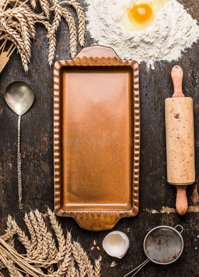 O molde rústico da galdéria do vintage vazio com o utensílio da cozinha para coze e as orelhas no fundo de madeira rústico foto de stock