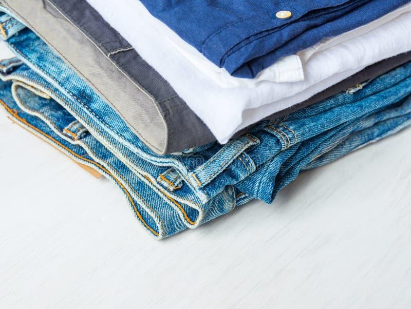 O montão da pilha do algodão dobrado das calças de brim arfa camisas azuis no fundo de madeira branco Prateleira do armário Estil imagens de stock