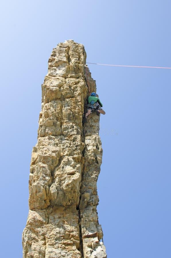 O montanhista de escalada em uma pedra calcária vertical balança contra um backgrou fotos de stock royalty free