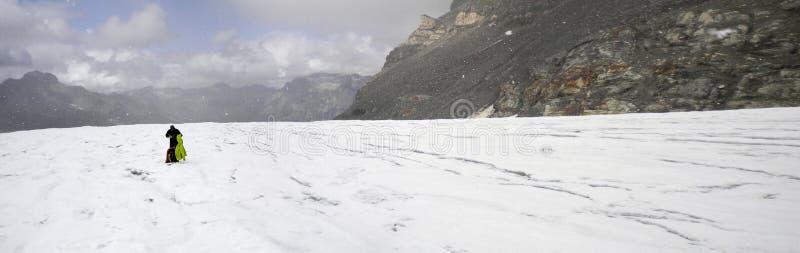 O montanhista de montanha obtém travado no mau tempo e põe sobre mais roupa enquanto está em uma geleira alpina alta com um grand imagens de stock