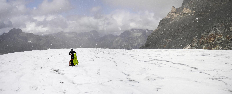 O montanhista de montanha obtém travado no mau tempo e põe sobre mais roupa enquanto está em uma geleira alpina alta com um grand fotos de stock royalty free