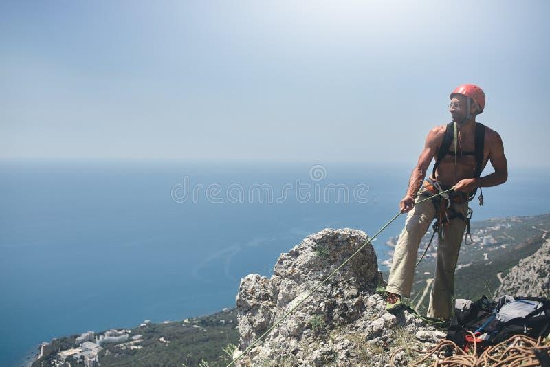 O montanhista de rocha do homem está na parte superior do penhasco foto de stock royalty free