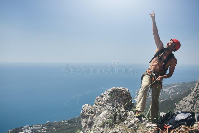 O montanhista de rocha do homem está na parte superior do penhasco fotografia de stock
